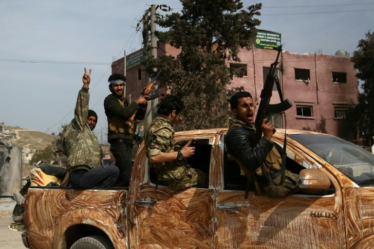 Turkish-backed Syrian rebels gather in the city of Afrin in northern Syria on March 18, 2018