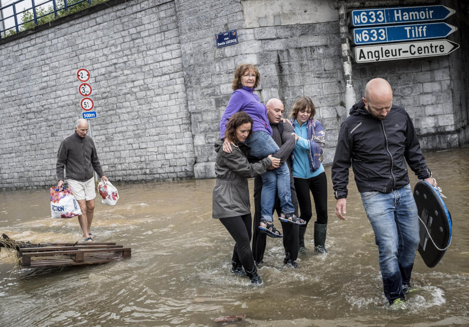 A woman is carried through a flooded street in Angleur, Province of Liege, Belgium, Friday July 16, 2021. Severe flooding in Germany and Belgium has turned streams and streets into raging torrents that have swept away cars and caused houses to collapse. (AP Photo/Valentin Bianchi)