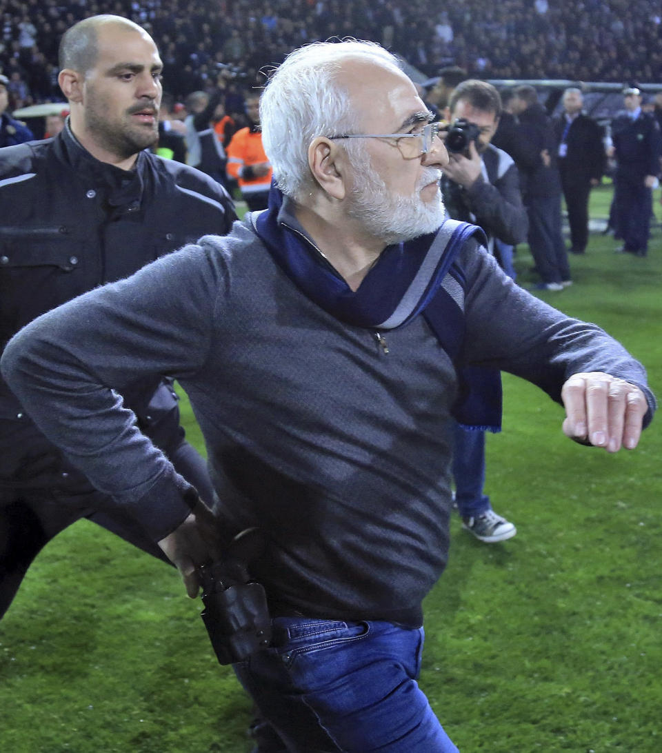 PAOK owner, businessman Ivan Savvidis invades into the pitch during a Greek League soccer match between PAOK and AEK Athens in the northern Greek city of Thessaloniki, Sunday, March 11, 2018. Savvidis came on the field twice and was accompanied by bodyguards. On the second occasion, without the overcoat he was wearing before, Savvidis appeared to be carrying a pistol which was in its holder. Savvidis made no move to use the weapon at any time. (InTime Sports via AP)