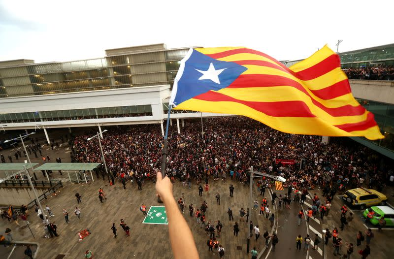 FILE PHOTO: A protester waves an Estelada (Catalan separatist flag) during a demonstration outside the airport in Barcelona