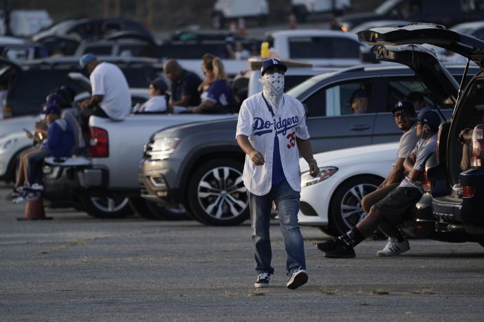 FILE - In this Oct. 20, 2020, file photo, fans sit in their cars outside of Dodger Stadium in Los Angeles to watch the television broadcast of Game 1 of baseball's 2020 World Series between the Los Angeles Dodgers and the Tampa Bay Rays. A backlog in coronavirus testing results hid a recent rise in infections in Los Angeles County, the county's top health official said Monday, Oct. 26, 2020, warning that fans gathering to watch recent championship sporting events may have increased the spread. (AP Photo/Ashley Landis, File)