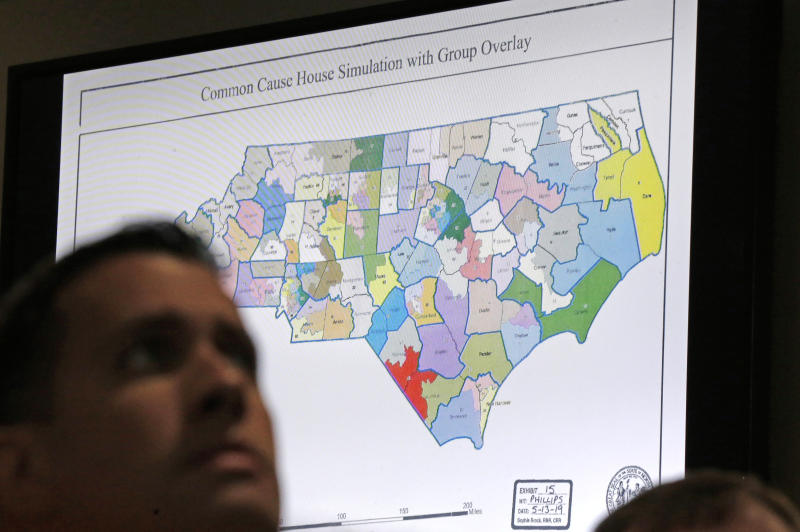 A districts map is shown as a three-judge panel of the Wake County Superior Court presides over the trial of Common Cause, et al. v. Lewis, et al at the Campbell University School of Law in Raleigh, N.C., Monday, July 15, 2019. (AP Photo/Gerry Broome)
