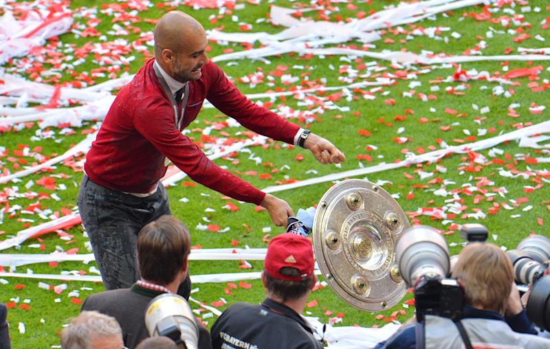 As Bayern head coach Pep Guardiola tries to pose for the photographers as the trophy falls down after Bayern Munich won the Bundesliga Championships in the Allianz Arena in Munich, Germany, on Saturday, May 10. 2014. (AP Photo/Kerstin Joensson)