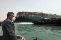 This photo released by the Suez Canal Authority on Thursday, March 25, 2021, shows Lt. Gen. Ossama Rabei, head of the Suez Canal Authority, investigating the situation with the Ever Given, a Panama-flagged cargo ship, after it become wedged across the Suez Canal and blocking traffic in the vital waterway. An operation is underway to try to work free the ship, which further imperiled global shipping Thursday as at least 150 other vessels needing to pass through the crucial waterway idled waiting for the obstruction to clear. (Suez Canal Authority via AP)