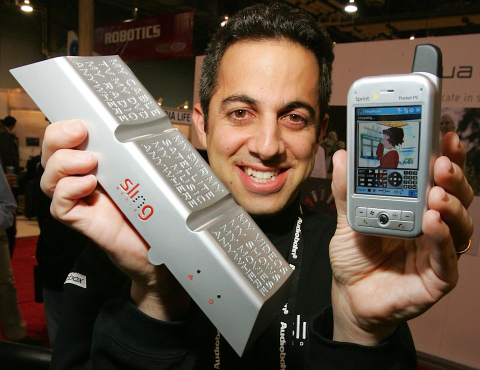 Sling Media co-founder Jason Krikorian displays the Slingbox (L) and a Sprint mobile device with SlingPlayer Mobile software playing a streaming image off his television set from his home at the International Consumer Electronics Show January 6, 2006 in Las Vegas, Nevada.