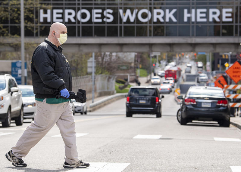 "A UPMC Shadyside employee, who declined to give his name, walks to a bus stop near UPMC Shadyside's overpass decorated with signage reading ""Heroes work here,"" during the COVID-19 pandemic Tuesday, April 21, 2020, in Pittsburgh. UPMC officials said Tuesday that patients coming into its hospitals would be tested for COVID-19 along with the system's medical staff, with the eventual goal of working with public health officials in broad public testing. (Steph Chambers/Pittsburgh Post-Gazette via AP)"