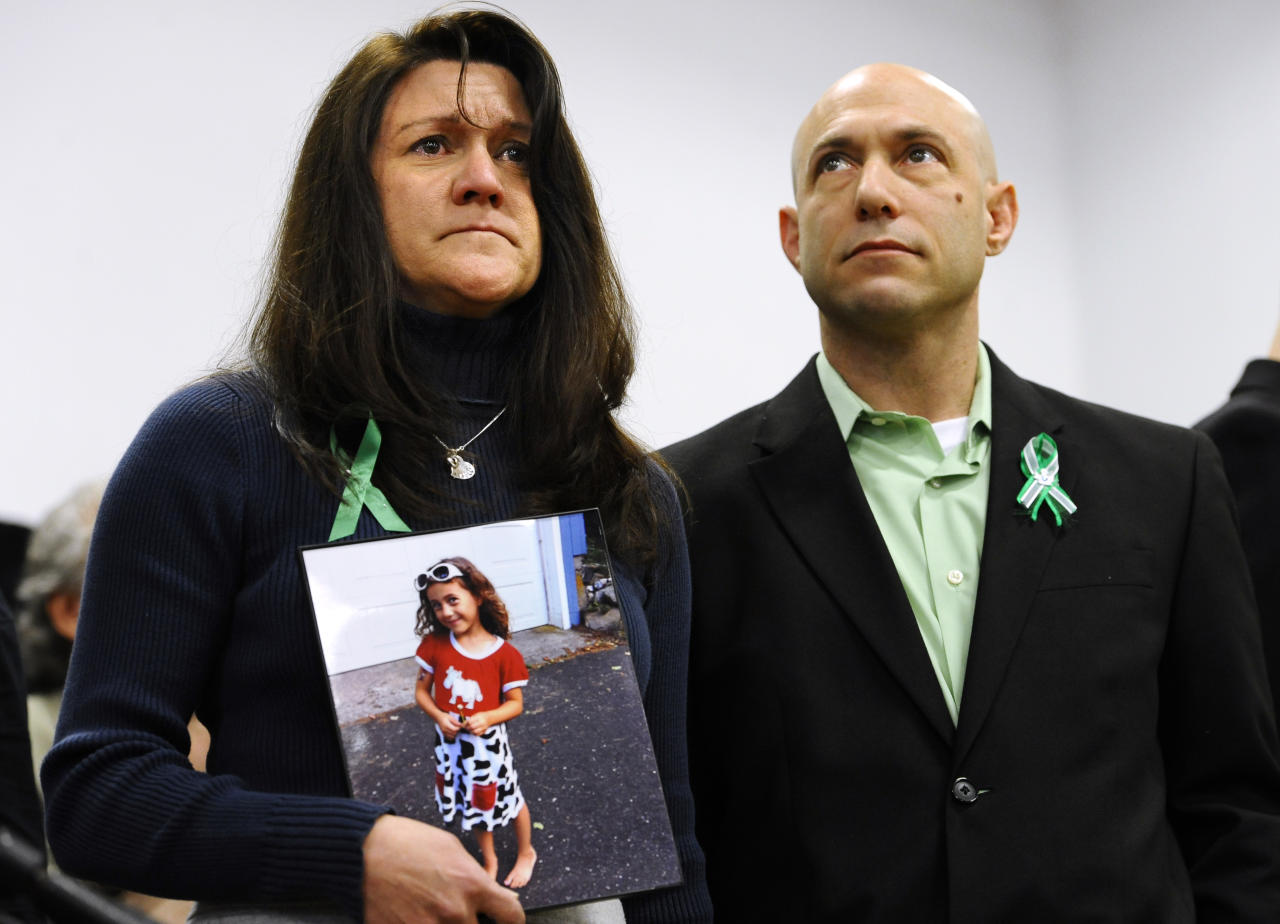 Jennifer Hensel, holding a portrait of her daughter, Sandy Hook School shooting victim Avielle Rose Richman, stands with her husband Jeremy Richman at a news conference at Edmond Town Hall in Newtown, Conn., Monday, Jan. 14, 2013. One month after the mass school shooting at Sandy Hook Elementary School, the parents joined a grassroots initiative called Sandy Hook Promise to support solutions for a safer community. (AP Photo/Jessica Hill)
