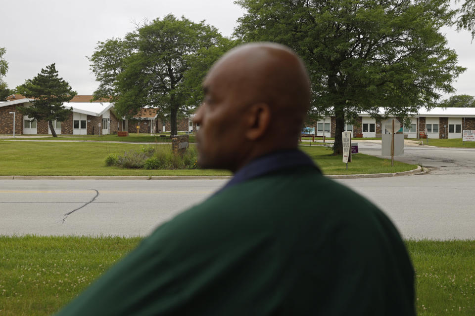 Crosby Smith, care provider at Ludeman Developmental Center, a state home for the developmentally disabled, looks towards the care center, Thursday, July 8, 2021 in Park Forest, Ill. Smith and his fiancee were among numerous staff and residents at the Ludeman Developmental Center who contracted the virus last year. He said the hazard money helped pay down credit cards and avoid further debt when buying clothing and shoes. (AP Photo/Shafkat Anowar)