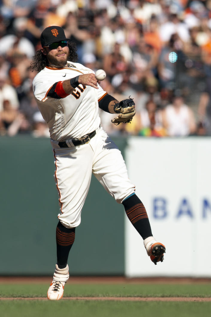 San Francisco Giants shortstop Brandon Crawford (35) leaves his feet to throw out San Diego Padres' Jake Cronenworth at first base during the eighth inning of a baseball game, Saturday, Oct. 2, 2021, in San Francisco. (AP Photo/D. Ross Cameron)