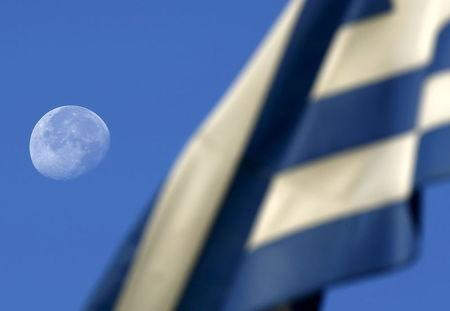 The moon sets behind a Greek flag over an elementary school used as polling station in Athens, Greece July 5, 2015. REUTERS/Yannis Behrakis