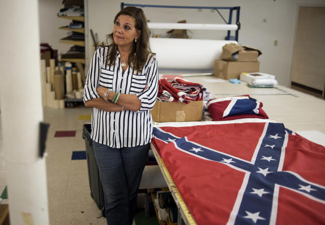 Belinda Kennedy, owner of Alabama Flag and Banner, stands by Confederate flags in the manufacturing area at her store on April 12, 2016, in Huntsville, Ala. Kennedy said the company, which sells American flags and manufactures Confederate flags, sold around 20,000 flags last year and about 12,000 of those were confederate flags. (Photo: Ty Wright/Getty Images)