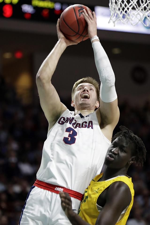 Gonzaga's Filip Petrusev (3) shoos as San Francisco's Josh Kunen defends during the first half of an NCAA college basketball game in the West Coast Conference men's tournament Monday, March 9, 2020, in Las Vegas. (AP Photo/Isaac Brekken)