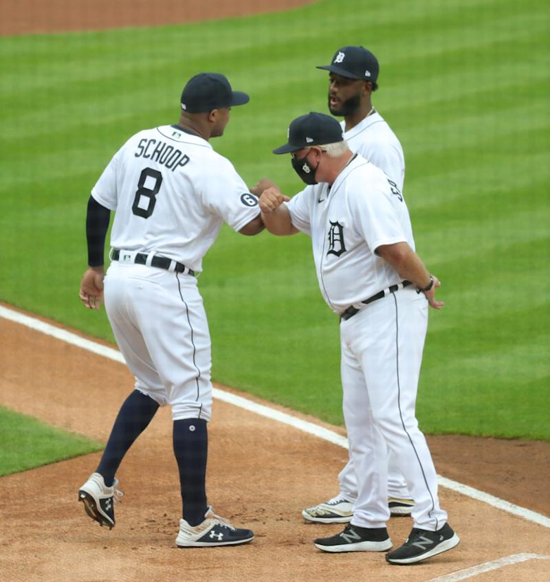 Tigers second baseman Jonathan Schoops elbow-bumps with Niko Goodrum and manager Ron Gardenhire before the Tigers' 14-6 loss to the Royals at Comerica Park on Monday, July 27, 2020.