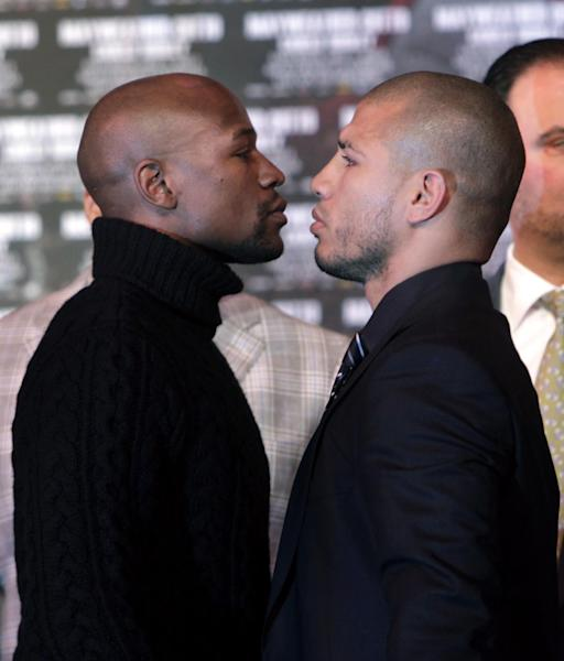 Boxers Floyd Mayweather, left, and Miguel Cotto face-off during a news conference in New York, Tuesday, Feb. 28, 2012. Cotto and Mayweather will fight in Las Vegas on May 5, 2012 for Cotto's WBA World super welterweight title. (AP Photo/Seth Wenig)