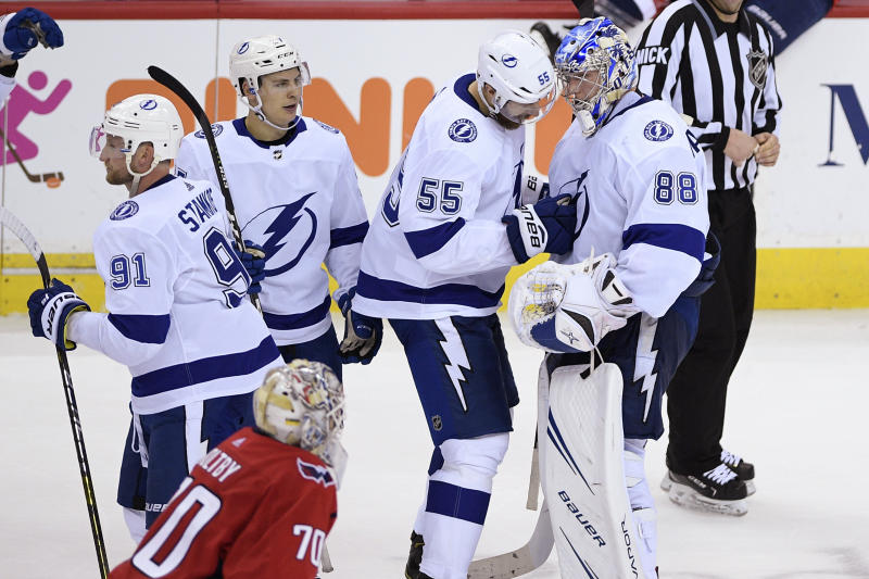 Tampa Bay Lightning goaltender Andrei Vasilevskiy (88), of Russia, celebrates with defenseman Braydon Coburn (55), center Yanni Gourde, second from left, and center Steven Stamkos (91) as Washington Capitals goaltender Braden Holtby (70) skates by after an NHL hockey game Wednesday, March 20, 2019, in Washington. The Lightning won 5-4 in overtime. (AP Photo/Nick Wass)