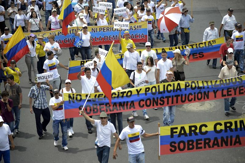 Demonstrators march on August 7, 2015, in Cali, Colombia against the government of President Juan Manuel Santos and the ongoing peace process with the Revolutionary Armed Forces of Colombia (FARC) guerrillas (AFP Photo/Raul Arboleda)