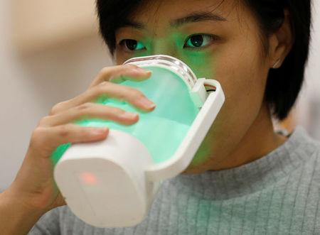 An NUS student tastes a virtual lemonade simulator, which uses electrodes to mimic the flavour and LED lights to imitate the color of real lemonade, at the National University of Singapore campus in Singapore