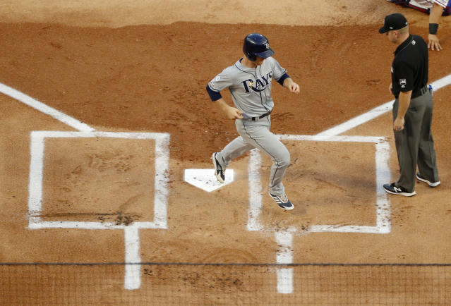 Tampa Bay Rays' Joey Wendle scores on a Tommy Pham double as umpire Tony Randazzo looks on in the first inning of a baseball game in Arlington, Texas, Wednesday, Sept. 11, 2019. (AP Photo/Tony Gutierrez)