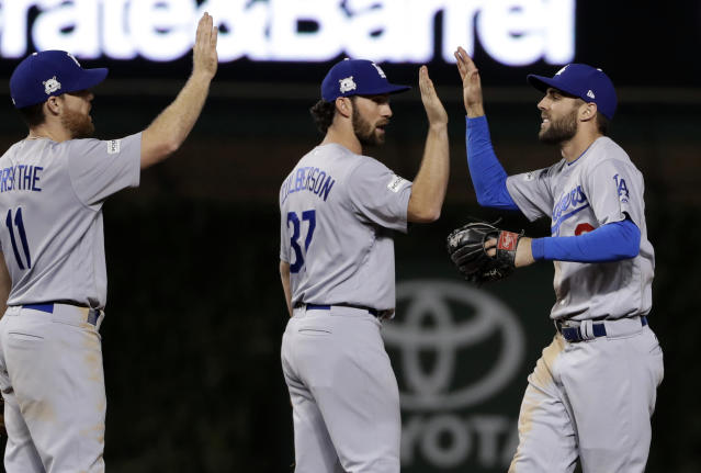 The Dodgers' Chris Taylor, right, celebrates with Charlie Culberson (37) and Logan Forsythe (11) after Game 3 Tuesday night. (AP)
