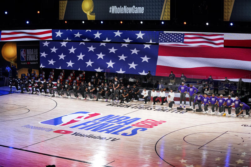 The Los Angeles Lakers and Miami Heat are seen on the court during the national anthem before Game 3 of basketball's NBA Finals, Sunday, Oct. 4, 2020, in Lake Buena Vista, Fla. (AP Photo/Mark J. Terrill)