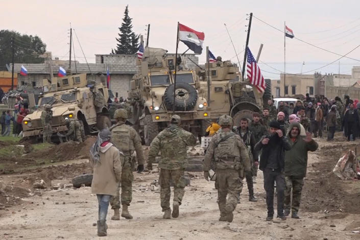 FILE - In this Feb. 12, 2020, file frame grab from video, Russian, Syrian and others gather next to an American military convoy stuck in the village of Khirbet Ammu, east of Qamishli city, Syria. Syria's civil war has long provided a free-for-all battlefield for proxy fighters. But in its ninth year, the war is drawing major foreign actors into direct conflict, with the threat of all-out confrontations becoming a real possibility. (AP Photo/File)