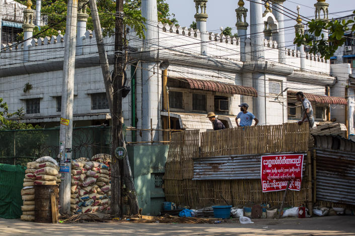 Residents watch as soldiers and police remove improvised barricades installed by anti-coup protesters and residents to secure a neighborhood from security forces in Yangon, Myanmar Thursday, March 18, 2021. (AP Photo)