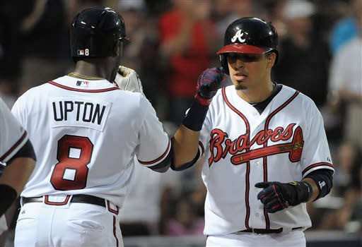 Atlanta Braves' Ramiro Pena is congratulated by Justin Upton (8) after Pena scored against the Toronto Blue Jays in the sixth inning of a baseball game at Turner Field in Atlanta, Thursday, May 30, 2013. (AP Photo/David Tulis)