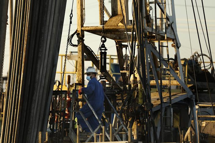 """In the Midway-Sunset oil field outside Taft, Calif., men work on well """"abandonment,"""" which is a process that renders an oil well closed for good. <span class=""""copyright"""">(Carolyn Cole / Los Angeles Times)</span>"""