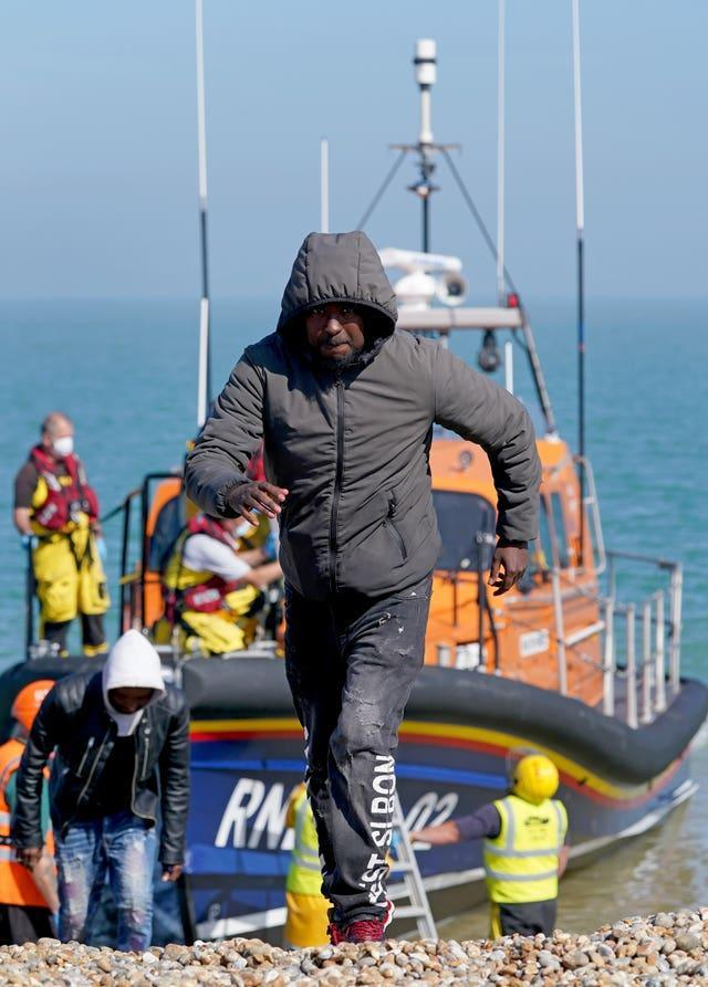 A group of people thought to be migrants are brought ashore from the Dungeness lifeboat in Kent