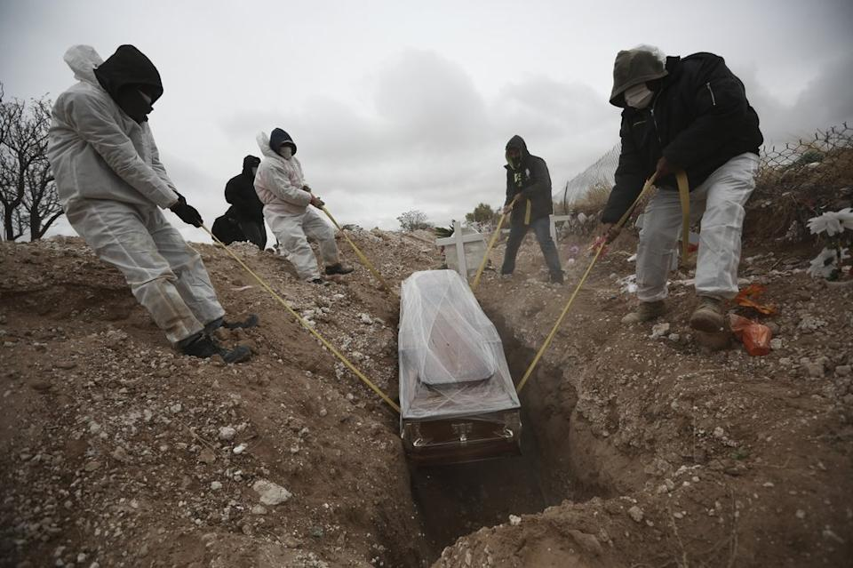 workers wearing full protection gear amid the new coronavirus pandemic, lower a coffin into a grave in an area of the San Rafael municipal cemetery set apart for people who have died from Covid-19