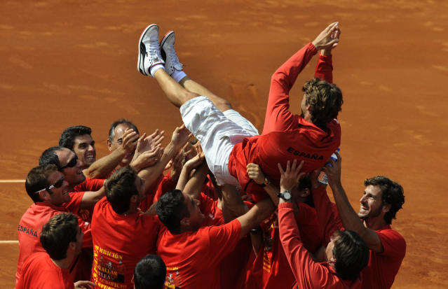 Juan Carlos Ferrero of Spain celebrates with his team mates after their victory over the U.S. at the Davis Cup semi-final at the Parque Hermanos Castro in Gijon, northern Spain September 16, 2012. REUTERS/Eloy Alonso (SPAIN - Tags: SPORT TENNIS)