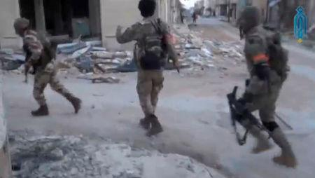 A still image taken from a video uploaded on social media on March 22, 2017, purports to show Tahrir al-Sham rebel fighters running with their weapons, said to be in Soran district, near Hama