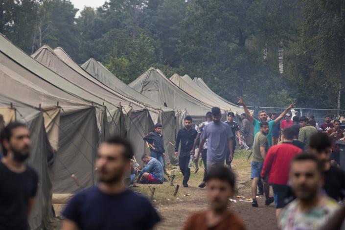 Migrants walk inside the newly built refugee camp in the Rudninkai military training ground, some 38km (23,6 miles) south from Vilnius, Lithuania, Wednesday, Aug. 4, 2021. The Red Cross warned Wednesday that Lithuania's decision to turn away immigrants attempting to cross in from neighboring Belarus does not comply with international law. Lithuania, a member of the European Union, has faced a surge of mostly Iraqi migrants in the past few months. Some 4,090 migrants, most of them from Iraq, have crossed this year from Belarus into Lithuania. (AP Photo/Mindaugas Kulbis)