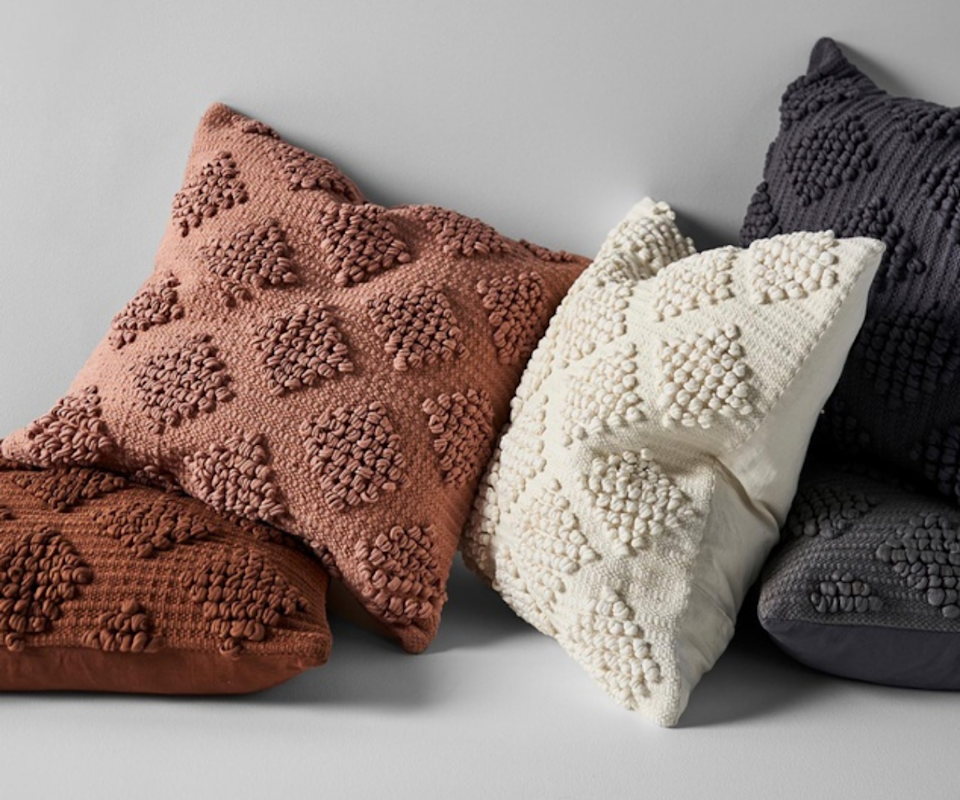 A collection of rust, cream and black textured cushions against a pale grey wall.
