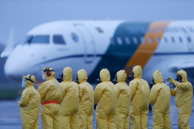 Soldiers wear protective suits during the arrival of Brazilians repatriated from Wuhan, China, the epicentre of the coronavirus outbreak (Beto Barata/AP)