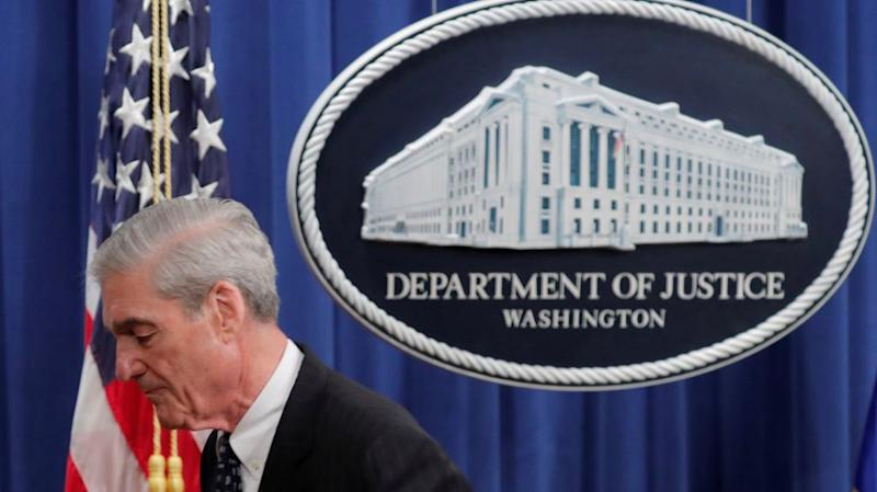 Robert Mueller at the DOJ by a US flag.