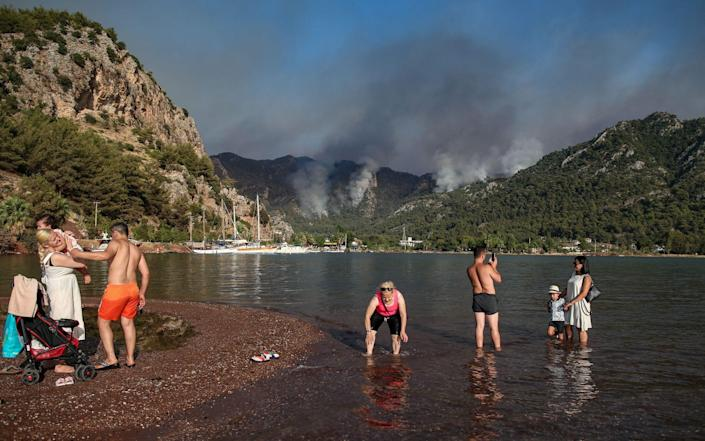People spend time at the sea backdropped by the wildfires burning in Marmaris - ERDEM SAHIN/EPA-EFE/Shutterstock