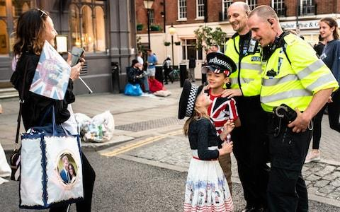 Young royal fans pose for a picture with police officers in Windsor - Credit: John Nguyen for The Telegraph