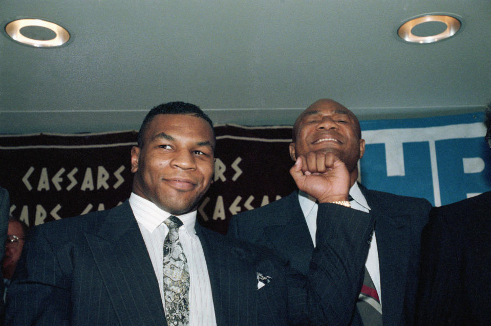 (Original Caption) 4/30/1990-New York, New York- Former world heavyweight champions Mike Tyson, (L), and George Foreman will appear on the same card in a boxing double-header extravanganza, June 16th, at Caesar's Palace in Las Vegas. They are pictured at a press conference.