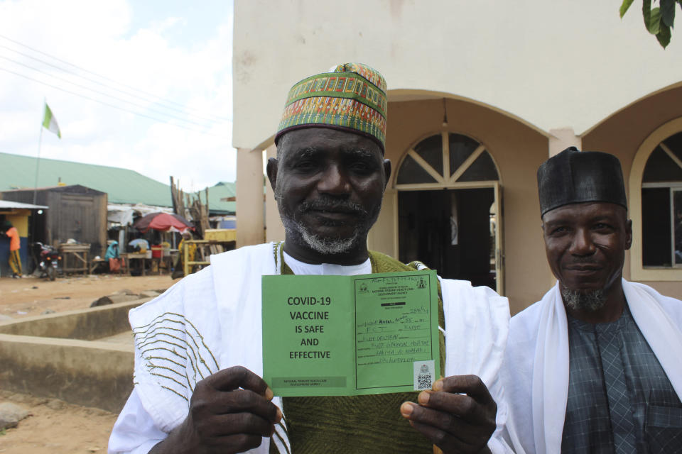 Yusuf Halilu Bisalla, deputy imam of Kuje Central Mosque, displays his Moderna COVID-19 vaccination certificate outside the Kuje, Central Mosque outskirts of Abuja, Friday, Oct. 8, 2021. Nigeria has begun the second rollout of COVID-19 vaccines as it aims to protect its population of more than 200 million amid an infection surge in a third wave of the pandemic. (AP Photo/Gbemiga Olamikan)