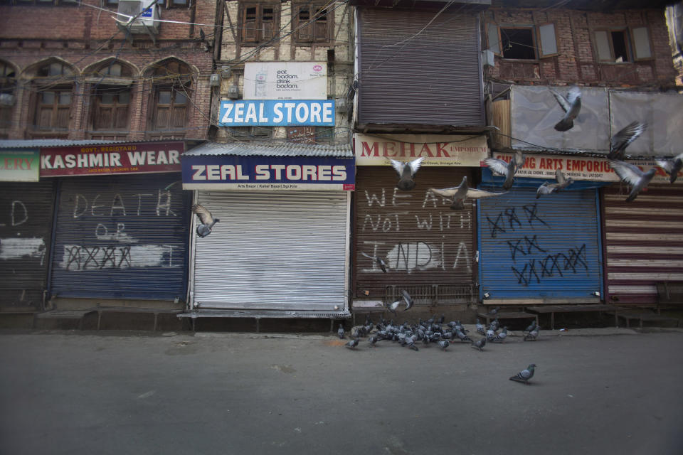 Pigeons fly at a deserted market area during lockdown to stop the spread of the coronavirus in Srinagar, Indian controlled Kashmir, July 22, 2020. Indian-controlled Kashmir's economy is yet to recover from a colossal loss a year after New Delhi scrapped the disputed region's autonomous status and divided it into two federally governed territories. (AP Photo/Mukhtar Khan)