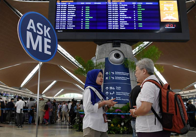 A MAHB Airport CARE Ambassador assists a passenger at KLIA in Sepang August 22, 2019, during a systems outage. — Bernama pic