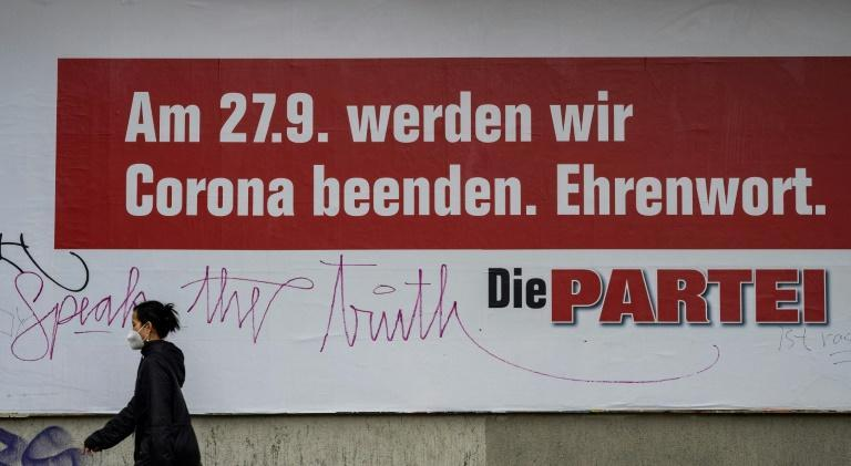 A woman walks past an election campaign poster for the satirical German political party 'Die Partei' reading 'On the 27th of September, we will put an end to Corona - Promise'