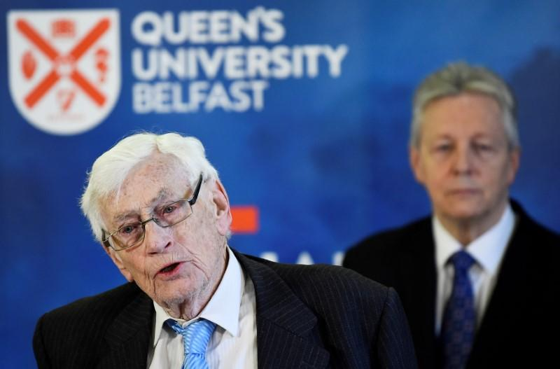 FILE PHOTO: Seamus Mallon speaks as Peter Robinson looks on at an event to celebrate the 20th anniversary of the Good Friday Agreement, in Belfast