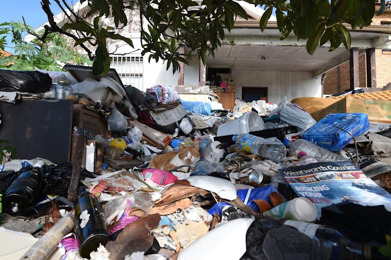 Pictured is the house known as the 'Bondi Hoarder's House', covered in rubbish as a cat sits out the front on a heap of rubbish has been forced to auction in 2015.