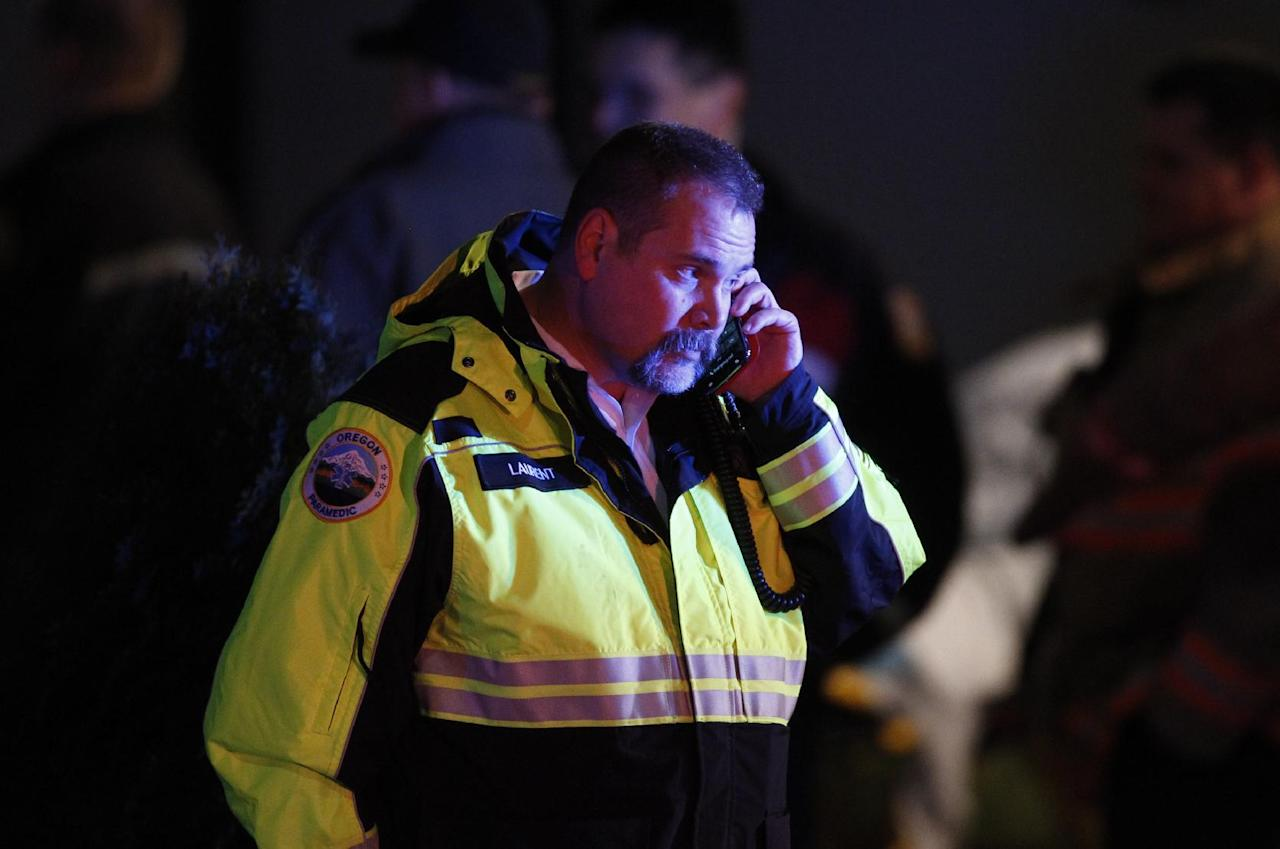 A paramedic talks on the phone outside Clackamas Town Center in Clackamas, Ore., where a shooting occurred Tuesday, Dec. 11, 2012. A gunman opened fire in the Portland, Ore., area shopping mall Tuesday, killing at least one person and wounding an unknown number of others, sheriff's deputies said. (AP Photo/The Oregonian, Bruce Ely) MAGS OUT; TV OUT; LOCAL TV OUT; LOCAL INTERNET OUT; THE MERCURY OUT; WILLAMETTE WEEK OUT; PAMPLIN MEDIA GROUP OUT
