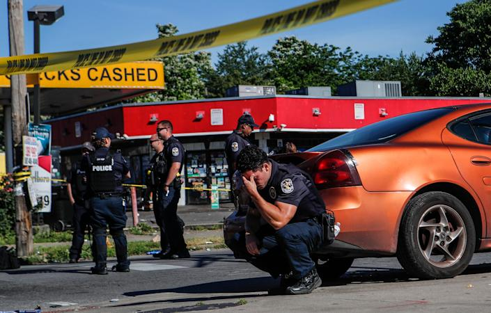 Louisville police were on guard inside police tape at the intersection of 26th and Broadway on June 1 after a man was shot and killed by police and National Guard personnel outside Dino's Market.