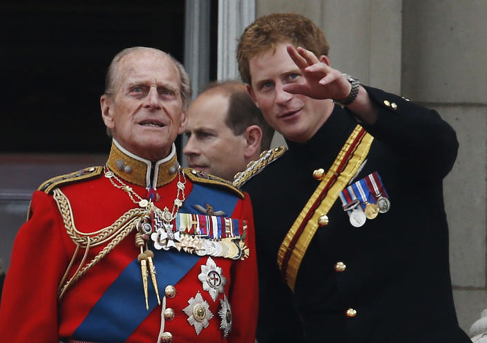 FILE - In this June 14, 2014 file photo, Britain's Prince Harry talks to Prince Philip as members of the Royal family appear on the balcony of Buckingham Palace, during the Trooping The Colour parade, in central London. Buckingham Palace officials say Prince Philip, the husband of Queen Elizabeth II, has died, it was announced on Friday, April 9, 2021. He was 99. Philip spent a month in hospital earlier this year before being released on March 16 to return to Windsor Castle. Philip, also known as the Duke of Edinburgh, married Elizabeth in 1947 and was the longest-serving consort in British history. (AP Photo/Lefteris Pitarakis, File)