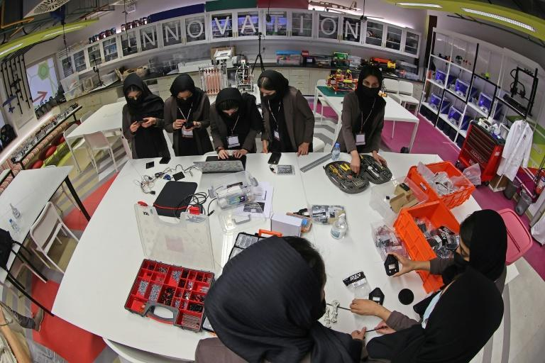 Members of an all-girl Afghan robotics team assemble components for a circuit board they are building, at the laboratory of Qatar's Texas A&M university in the capital Doha (AFP/KARIM JAAFAR)