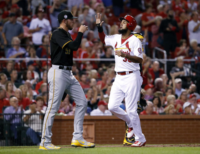 St. Louis Cardinals' Jose Martinez, right, celebrates as he scores past Pittsburgh Pirates starting pitcher Joe Musgrove during the first inning of a baseball game Tuesday, Sept. 11, 2018, in St. Louis. (AP Photo/Jeff Roberson)